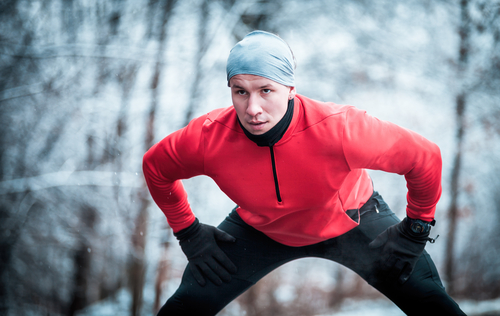 runner stretching in cold weather