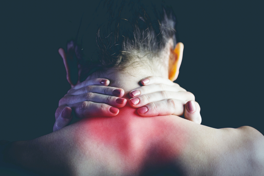 Woman with muscle injury holding neck