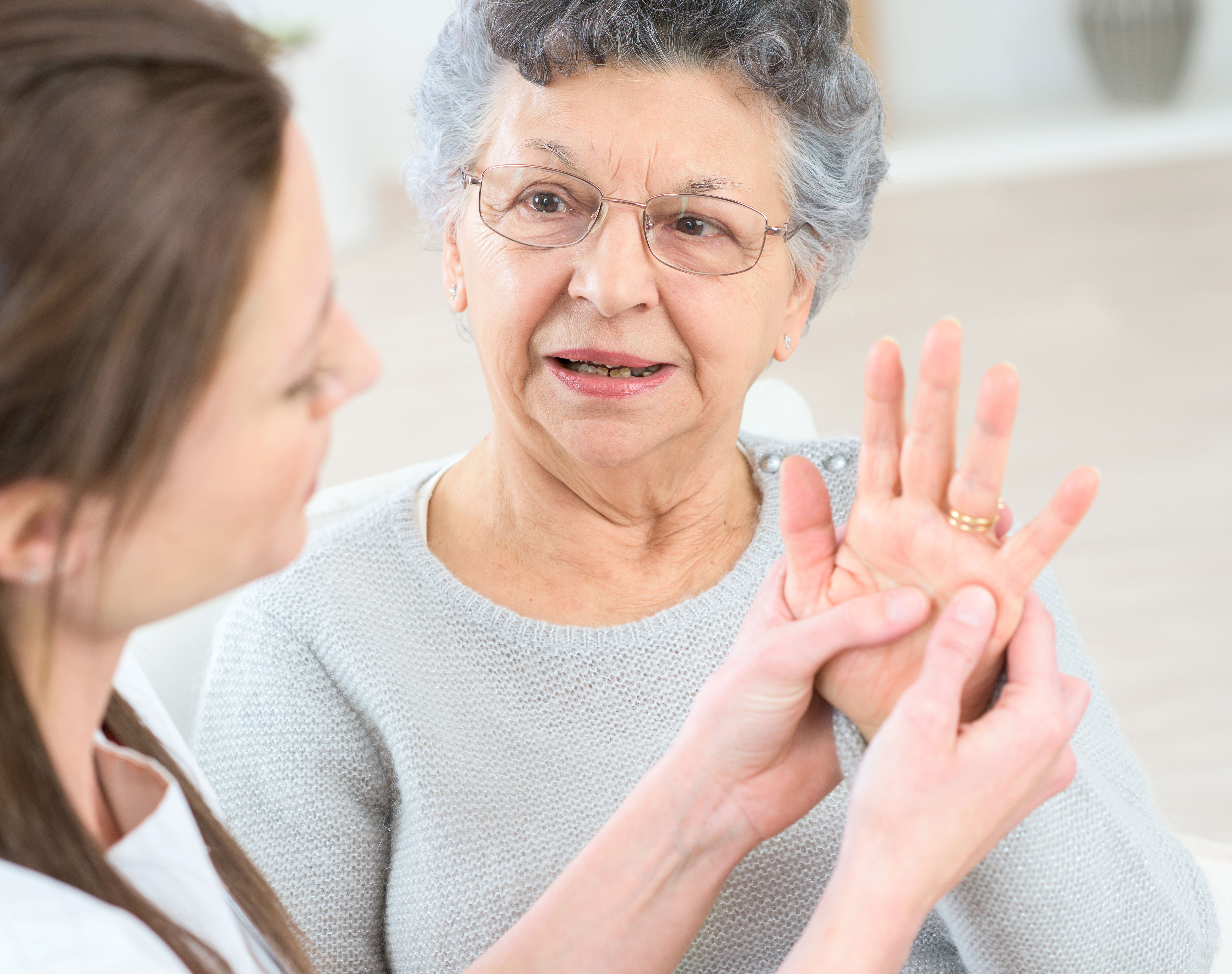 Physical therapist helping elderly woman with hand pain