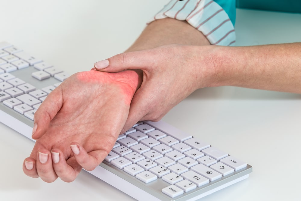 Woman at desk holding wrist in pain from carpal tunnel syndrome