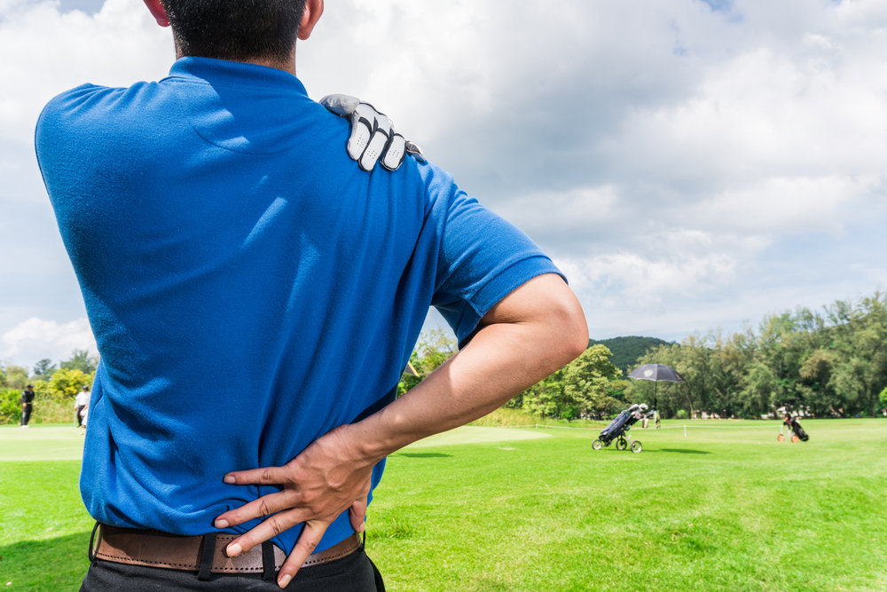 man with back pain playing golf