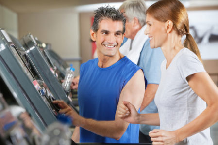 physical trainer coaching runner on treadmill