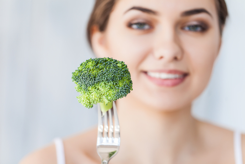 woman holding broccoli on fork