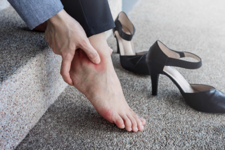 woman sitting on stairs with heel pain