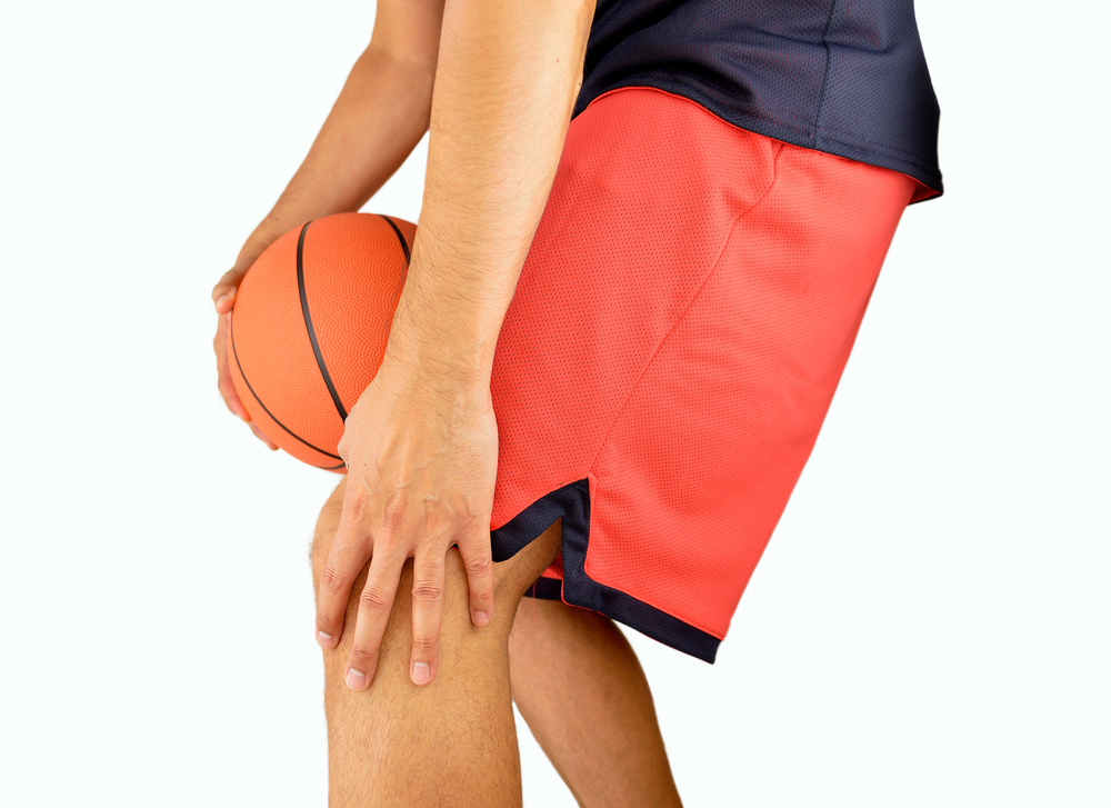 injured basketball player holds knee