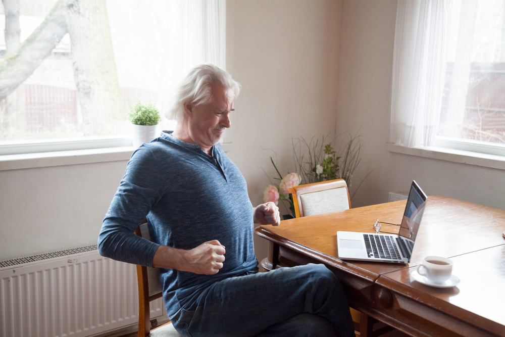 Grey haired middle aged senior male sitting alone in the kitchen on chair stretching back after long time working on computer doing exercises for loins preventing osteoarthritis and spinal stenosi