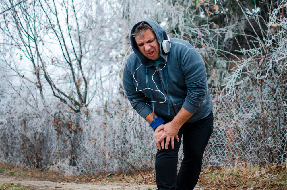 man with pain in the knee while running outdoors in cold day