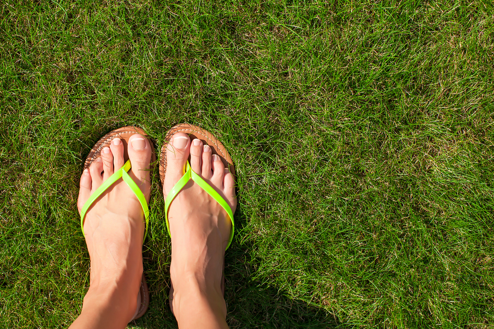 feet in flip flops on the grass
